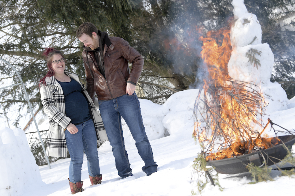 Futurs parents devant un feu de bois